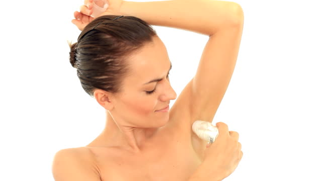 Young attractive woman using an antiperspirant, isolated on white video