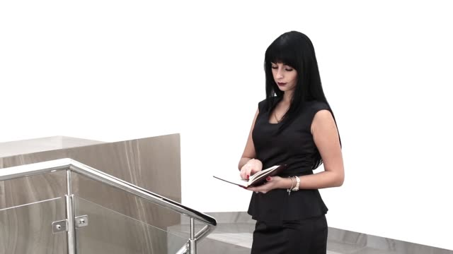 Young Attractive woman walking in a office, reading information in notebook.
