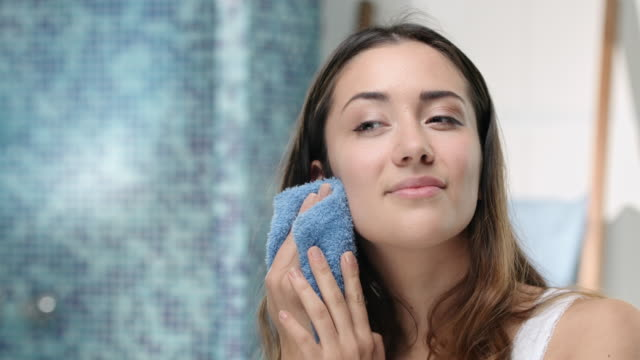 young attractive woman washes her face with a face towel - trattamento per la pelle video stock e b–roll