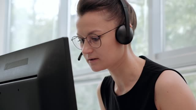 a young attractive woman wearing a black jacket in a black jacket is sitting at her desk in a executive chair. holds a video conference in headphones with a microphone. - zestaw głośnomówiący filmów i materiałów b-roll
