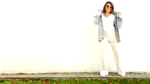 Young attractive woman wearing all white, sunglasses and denim jacket posing before white wall.