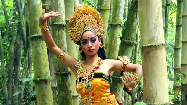 Young Balinese dancer performing Legong dance in a bamboo forest