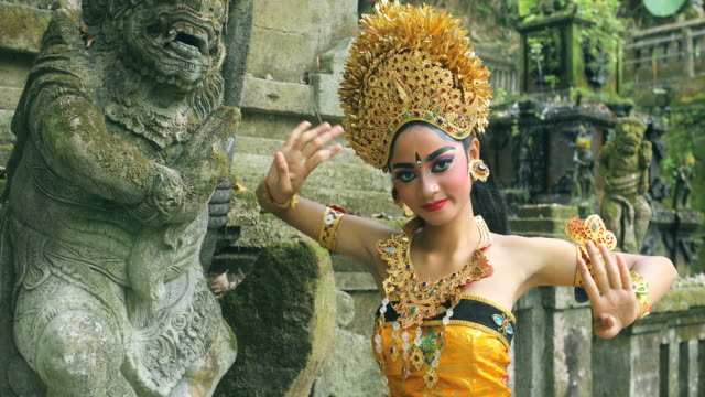 young balinese dancer performing legong dance in a hindu temple - bali filmów i materiałów b-roll