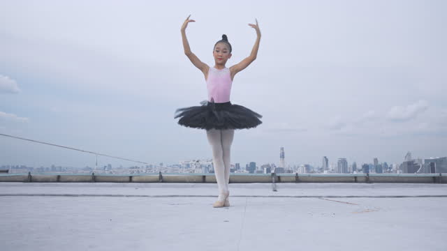 Young ballerina and ballet dancing on top building,  Graceful woman spinning in ballet Young ballerina and ballet dancing on top building,  Graceful woman spinning in ballet effortless stock videos & royalty-free footage