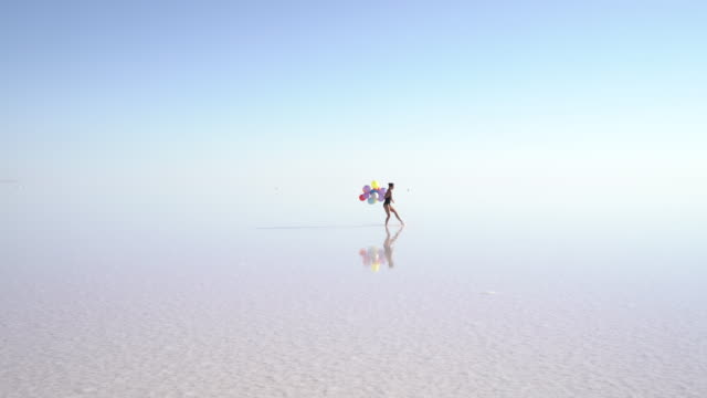 Young ballerina dancing on the lake with color balloons video