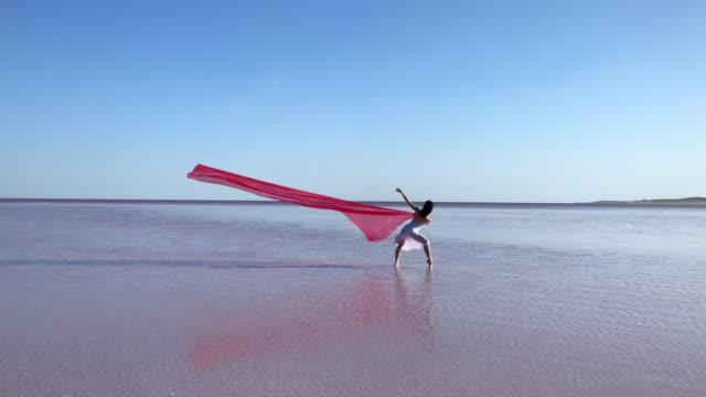 vídeos de stock, filmes e b-roll de jovem bailarina dançando no lago com tule vermelho à noite. - tule têxtil