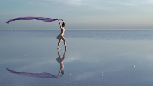 vídeos de stock, filmes e b-roll de jovem bailarina dançando sobre o lago de sal com tule cor - arte, cultura e espetáculo