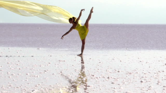 young ballerina dancing on the salt lake with color tulle - тюль ткань стоковые видео и кадры b-roll