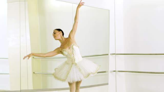 ung ballerina klädd i vit tutu dansa på hennes pointe ballet skor. 4k - piruett bildbanksvideor och videomaterial från bakom kulisserna