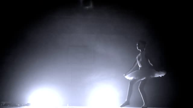 young ballerina girl in tutu bounces in slow motion moving her legs and crouching at the end in a smoky room with a spotlight in the background - tutù video stock e b–roll