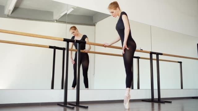 junge ballerina in schwarzem trikot und spitzenschuhe beim aufwärmen an der barre im ballett-tanzstudio, tracking-shot - gymnastikanzug stock-videos und b-roll-filmmaterial
