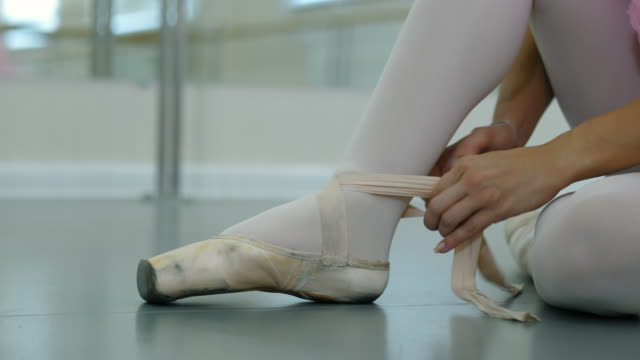 Young ballerina in tutu costume wraps white silk ribbons of soft top ballet shoes pointe and ties them up. Woman preparing for dance training lessons in gym. 4k