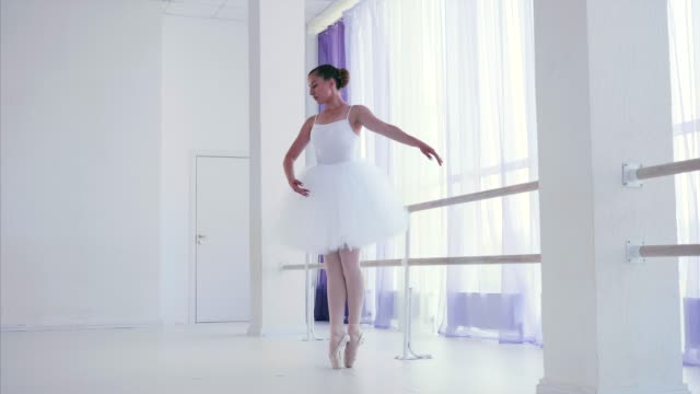 Young ballerina is training ballet element near the barre stand in dance class. Professional ballet dancer in white tutu and pointes is training ballet element near the barre stand in dance class. She is lifting her leg high back, arching her spine. ballet dancer stock videos & royalty-free footage