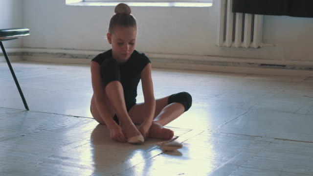 Young ballerina putting on her ballet shoes on the wooden floor video
