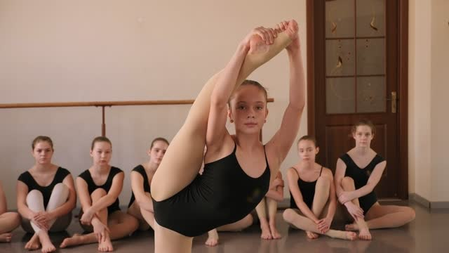 A young ballerina shows a complex gymnastic exercise in a ballet Studio. A young ballerina shows a complex gymnastic exercise in a ballet Studio, with a group of ballerinas sitting on the floor in the background. doing the splits stock videos & royalty-free footage