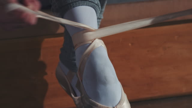 junge ballerina binden ihren ballettschuh im studio - ballettschuh stock-videos und b-roll-filmmaterial