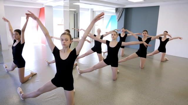 Young ballerinas dressed in black uniform stand in pose in dancing class video
