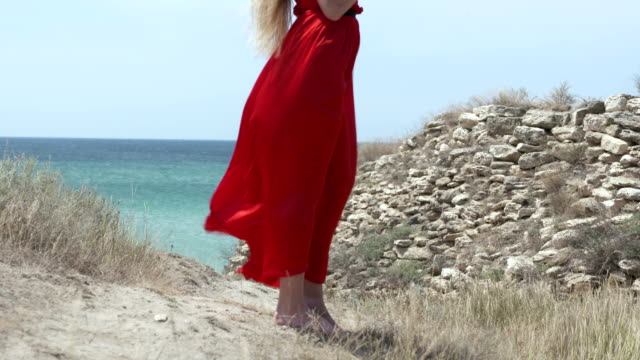 Young barefoot girl in long red dress on footpath leading to the beach video