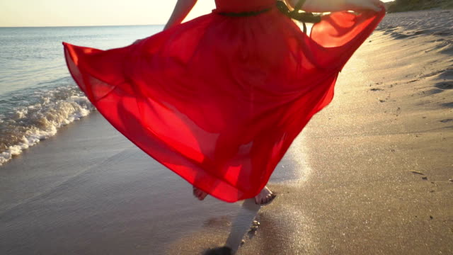 Young barefoot girl in long red dress running and dancing along the surf line Young barefoot girl in long red dress running dancing along the surf line. Happy girl with long hair having fun on sandy beach during summer holidays. Female bare feet and fluttering dress at sunset. dress stock videos & royalty-free footage