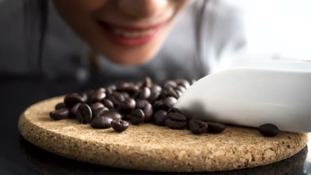 Young barista smelling coffee beans laying on table with smiley face Young barista smelling coffee beans laying on table with smiley face smelling stock videos & royalty-free footage