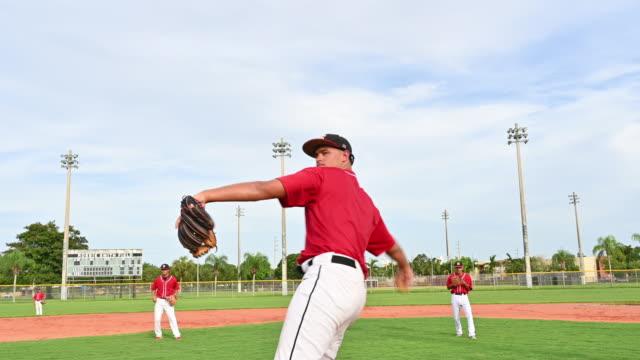 vídeos de stock, filmes e b-roll de jovem arremessador de beisebol jogando campo de treino - boné