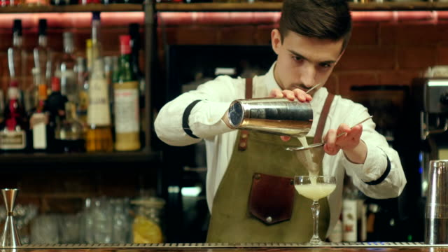 Young bearded barman prepare cocktail drink using two types of alcohol, sweet syrup in unusual glass, and decorating it video