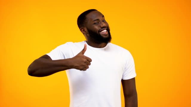 young bearded black guy giving thumbs up, smiling at camera on yellow background - kciuk filmów i materiałów b-roll