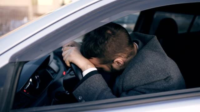Barbu de jeune homme d'affaires assis dans la voiture très en colère et a souligné après que échec dur et se déplacer dans les embouteillages - Vidéo