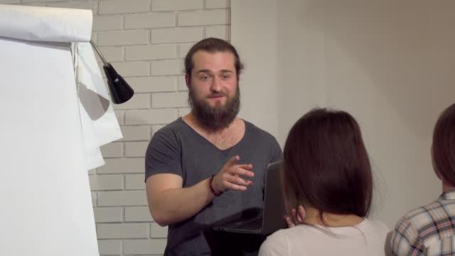 Joven hombre de negocios barbudo liderando una reunión con colegas en la oficina - vídeo