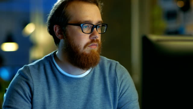 Young Bearded Creative Man Thinks on a Problem While Working on His Personal Computer. video