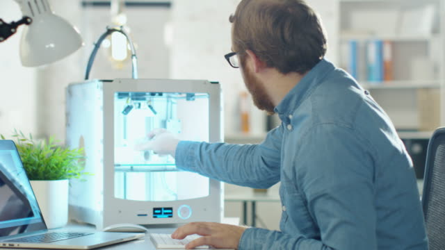 Young Bearded Engineer Expects 3D Model that He Just Created in His 3D Printer. He Sits at His Desk in Modern Office. - vídeo