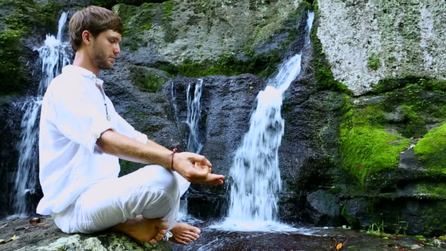 Young bearded man doing meditation near a waterfall video