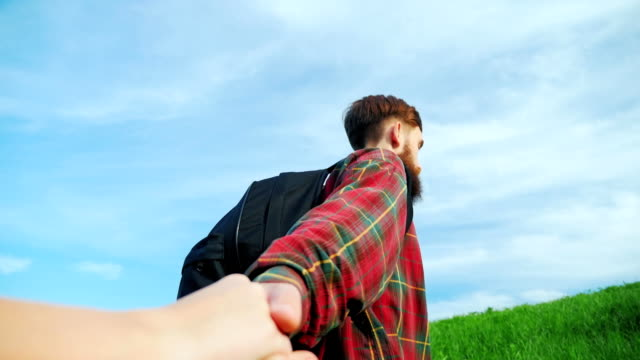 A young bearded man helps climb a mountain friend. Helping hand video