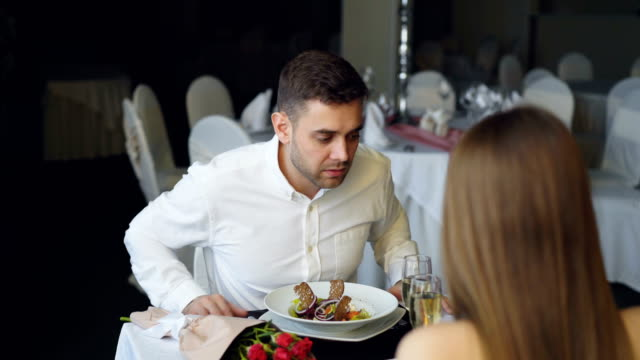Young bearded man is arguing with his girlfriend while dining in restaurant then leaving. Lovers quarrel, negative emotions and relationship crisis concept. Young bearded man in white shirt is arguing with his girlfriend while dining in restaurant then leaving. Lovers quarrel, negative emotions and relationship crisis concept. relationship breakup stock videos & royalty-free footage