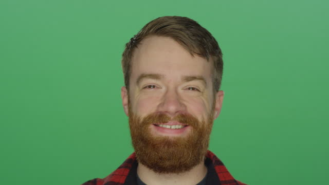 Young bearded man laughs and smiles, on a green screen studio background video
