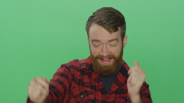 Young bearded man smiling and dancing, on a green screen studio background video