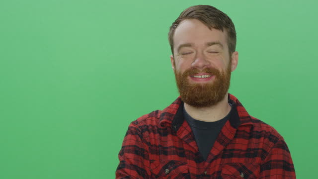 Young bearded man smiling, on a green screen studio background Young bearded man smiling, on a green screen studio background plaid stock videos & royalty-free footage