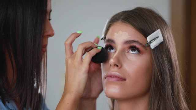 vídeos de stock e filmes b-roll de young beautician blending foundation make-up with a sponge - esponja