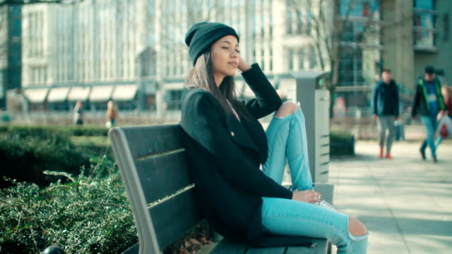 Young beautiful african american woman sitting on a bench. Stylish cheerful woman relaxing in a city during sunny day. park bench stock videos & royalty-free footage