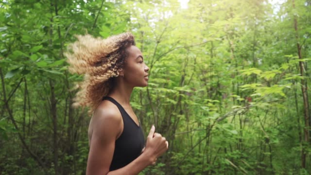 young beautiful african american woman with curly hair running in a forest, close up - woman portrait forest video stock e b–roll