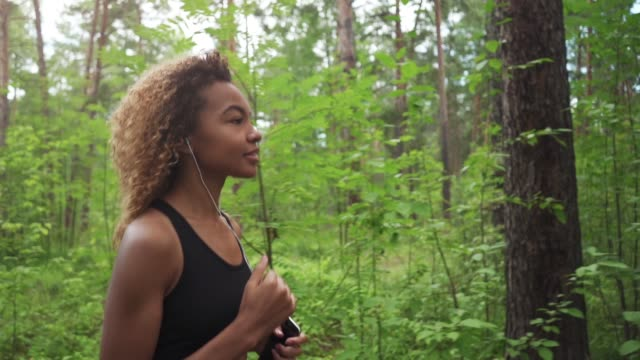 young beautiful African American woman with curly hair running with music in a forest, close up