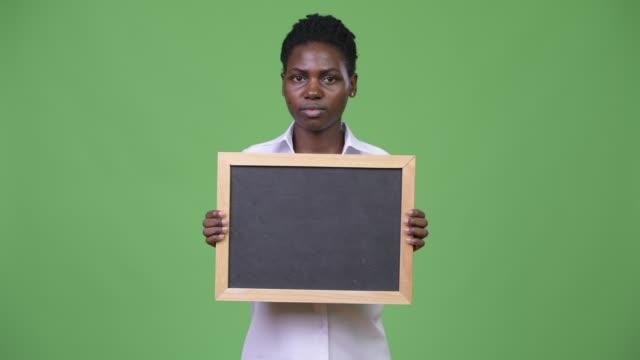 unga vackra afrikanska affärskvinna holding blackboard - tjänstekvinna bildbanksvideor och videomaterial från bakom kulisserna