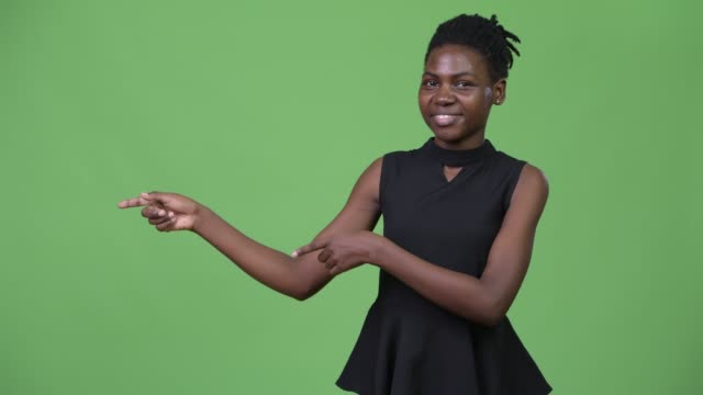 vídeos de stock e filmes b-roll de young beautiful african businesswoman showing something - apontar sinal manual