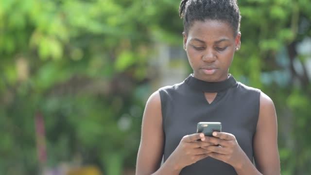 unga vackra afrikanska affärskvinna använder telefonen utomhus - tjänstekvinna bildbanksvideor och videomaterial från bakom kulisserna