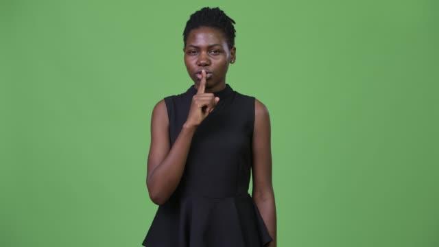 unga vackra afrikanska affärskvinna med finger på läppar - tjänstekvinna bildbanksvideor och videomaterial från bakom kulisserna