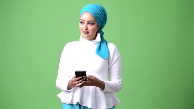 unga vackra afrikanska muslimsk kvinna mot färgnyckel med grön bakgrund - anständig klädsel bildbanksvideor och videomaterial från bakom kulisserna