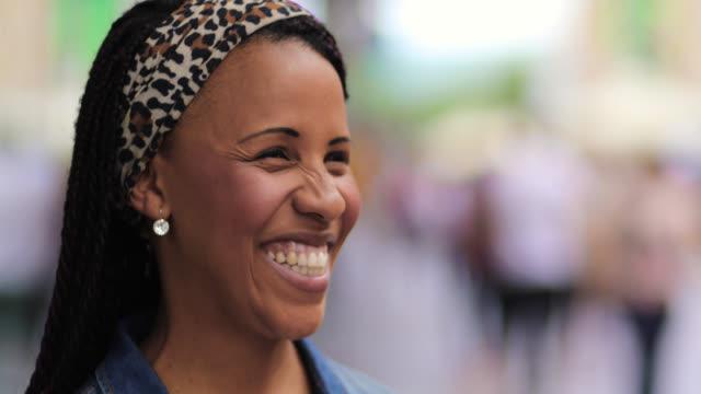 junge schöne afroamerikanische frau setzen sonnenbrille auf und lächelnd - ohrring stock-videos und b-roll-filmmaterial