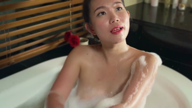 ung vacker och lycklig asiatisk koreansk kvinna glad i badkar med skum bubblor bad hemma eller hotell badrum leende avslappnad njuter lyx livsstil - japanese bath woman bildbanksvideor och videomaterial från bakom kulisserna