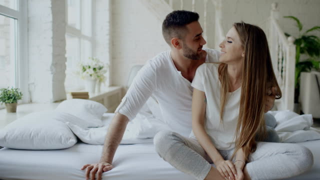 Young beautiful and loving couple embrace and kisisng while sitting on bed after waking up in the morning video
