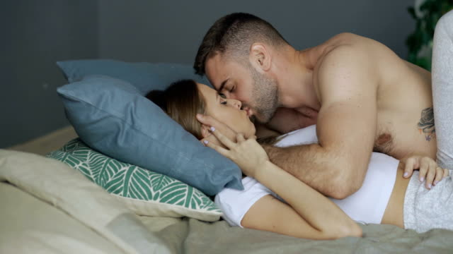 Young beautiful and loving couple kissing on bed in the morning Young beautiful and sexy couple kissing on bed in the morning sexual activity sex naked couple stock videos & royalty-free footage
